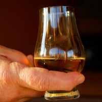 Hand holding glass of whisky